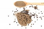 Black peppercorns and milled in wooden spoon.