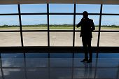 Businessman Using Mobile Phone Against Airport Window