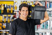 Portrait of confident young man carrying toolbox on shoulder in hardware store