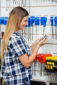 Side view of woman checking information of screwdriver on mobilephone in hardware store