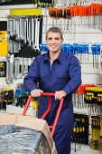 Portrait of mature worker in overalls pushing trolley in hardware shop