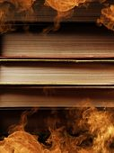 Pile of hardcover books surrounded with swirling tendrils smoke or vapor in a darkened vintage style