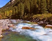 Pastoral in the Alpine mountain valley in Austria. Rapid mountain stream. Cascades of cold water at