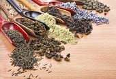 assortment of dry tea in scoops on wooden table background