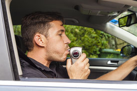 picture of youg  - Youg man in car blowing into breathalyzer - JPG