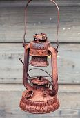 Old Rusted Red Kerosene Lamp On Gray Wooden Wall