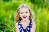 stock photo of fanny  - Fanny and beautiful laughing little girl with long blond curly hair outdoor portrait in summer park on bright sunny day. 