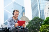 picture of casual wear  - Man talking on tablet pc having video chat conversation in sitting outside using app on 4g wireless device wearing headphones - JPG