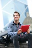 Urban young professional man using tablet computer sitting in Hong Kong outside using app on 4g wireless device wearing headphones. Casual young urban professional male in his late 20s.