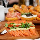 Sliced salmon with roe and arugula on table, close-up