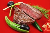 meat food : roasted fillet mignon on red plate with tomatoes apples and chili pepper isolated over white background