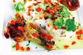 chicken drumsticks with mash on white plate