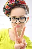 Portrait of girl in colorful clothes and cap doing funny faces