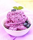 Ice cream blueberry with mint in bowl on purple napkin