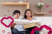 Couple on the couch opening parcel against hearts