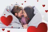 Couple wrapped in the duvet against hearts