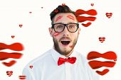 Geeky hipster with kisses on his face against hearts