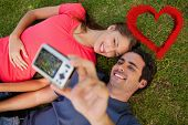 Man taking a photo with his friend while lying side by side against red smoke heart