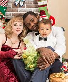 Happy Family: Black Father, Mom And Baby Boy By Fireplace. Christmas And New Year