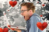 Geeky businessman using his laptop against grey valentines heart pattern
