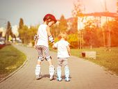 stock photo of little sister  - two little sisters to roller skate on the street - JPG