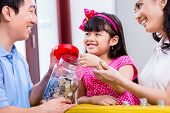 stock photo of coins  - Chinese family saving money for college fund of child - JPG