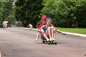 pic of driveway  - Girls having fun skateboarding home driveway with dogs - JPG