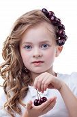Freckled girl with cherries posing at camera