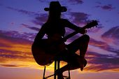 Silhouette Of A Woman With A Guitar Sit Play