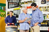 picture of hardware  - Father and son checking checklist on clipboard while worker working in background at hardware store - JPG