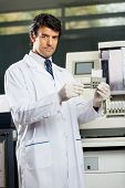 Portrait of confident mid adult male scientist analyzing urine samples in laboratory