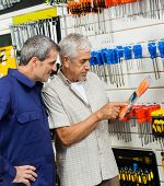 Senior customer examining packed screwdriver while vendor looking at it in hardware shop