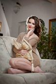 Young sensual woman sitting on sofa relaxing. Beautiful long hair girl with comfortable clothes