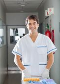 Happy young male technician pushing medical cart in hospital hallway