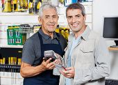 Portrait of senior salesman accepting payment through NFC technology from customer in hardware store