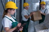 stock photo of labourer  - Female manufacturing labourer holding clipboard and noting - JPG