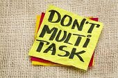do not multitask - efficiency advice on a sticky note against burlap canvas