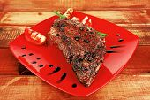 meat over white : grilled meat shoulder on red plate with tomatoes green lettuce over wooden table