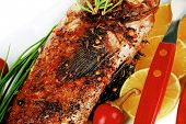served main course isolated on white: whole fried seabass on plate with lemons,tomatoes and peppers