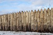 stock photo of log fence  - Old weathered wooden fence in the village winter time - JPG
