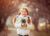 cute smiling  little girl smiling and holding a bouquet of blue  snowdrops