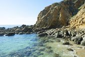 A small, secluded ocean front cove with large, smooth boulders embraces gentle surf bouncing off the large rocks