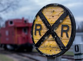 picture of caboose  - Old fashioned wooden RR Railroad warning sign with red caboose in background in Warrenton Virginia - JPG