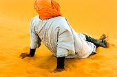 picture of camel  - Camel driver resting on sand dune after work in the Moroccan desert - JPG