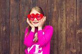 stock photo of big-girls  - Funny portrait of a cute little girl wearing big heart shaped sun glasses - JPG