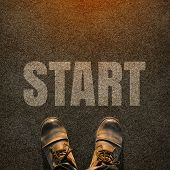 stock photo of foot  - A pair of feet on a tarmac road with white print of the word start for the concept of starting point - JPG
