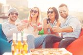 picture of foreground  - Four young cheerful people showing their thumbs up and smiling while sitting on bean bags at the outdoors terrace with pizza and beer laying on foreground - JPG