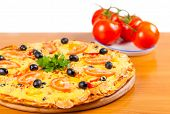 picture of hot fresh pizza  - hot fresh a pizza with tomatoes on a wooden background - JPG