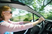 Постер, плакат: Smiling Beautiful Woman In Sunglasses Driving Car At High Speed