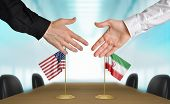 stock photo of extend  - Two diplomats from the United States and Iran extending their hands for a handshake on an agreement between the countries - JPG